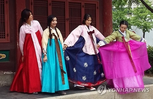Foreign travelers show off their hanbok during their visit to a traditional village in Seoul on July 3, 2016. (Yonhap)