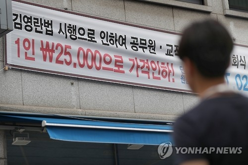A restaurant in eastern Seoul advertises a price reduction on an outdoor placard to adapt to the era of the Kim Young-ran law. (Yonhap file photo)