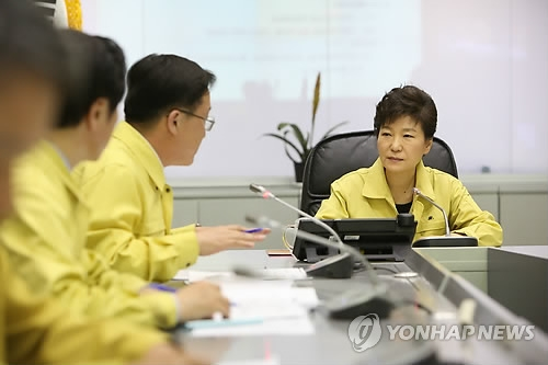 This photo, provided by the presidential office Cheong Wa Dae, shows President Park Geun-hye (R) being briefed on the sinking of the ferry Sewol at the government disaster control agency in Seoul on April 16, 2014. (Yonhap)