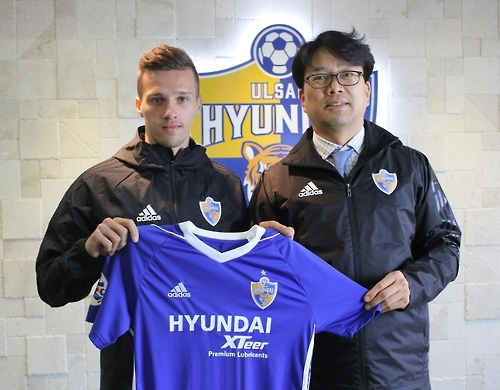 In this photo provided by Ulsan Hyundai on Feb. 9, 2017, Croatian attacker Mislav Orsic (L) holds Ulsan Hyundai jersey with the club's general manager Kim Gwang-guk after signing a contract with the South Korean football club in Ulsan. (Yonhap)
