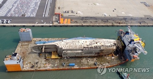 In this file photo, the Sewol ferry, lifted from where it sank some three years ago in the country's southwestern waters, is brought to a port in Mokpo, on March 31, 2017. The ill-fated ship will be put on dry dock, and a search will begin to find the remains of nine people still missing from the sinking on April 16, 2014. (Yonhap)