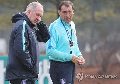 In this file photo, taken on March 24, 2017, South Korean men's national football team head coach Uli Stielike (L) speaks with his assistant Carlos Alberto Armua during the team's training at the National Football Center in Paju, Gyeonggi Province. (Yonhap)