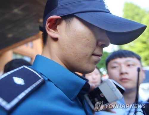 South Korean singer and actor T.O.P of boy band BIGBANG, who is serving his mandatory military service as a conscripted policeman, leaves his workplace in Seoul surrounded by reporters questioning his marijuana charges on June, 5, 2017. (Yonhap)