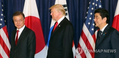 South Korean President Moon Jae-in (L), U.S. President Donald Trump (C) and Japanese Prime Minister Shinzo Abe head to the venue for their three-way meeting held at the U.S. consulate in Hamburg, Germany on July 6, 2017. (Yonhap)