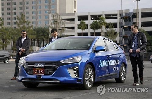 In this undated photo provided by Hyundai Motor on Dec. 20, 2016, members of the media look at the autonomous version of the carmaker's Ioniq ahead of a self-driving road test in Las Vegas. The test, held on Dec. 15, covered real-life street driving in the daytime and at night over a distance 4 kilometers. (Yonhap)