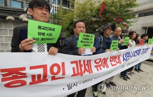 In this file photo, a group of activists from the Korea Taxpayers' Association hold a protest rally in front of the State Affairs Planning Advisory Committee building in central Seoul on May 31, 2017, demanding that religious leaders pay taxes like all waged workers. (Yonhap)