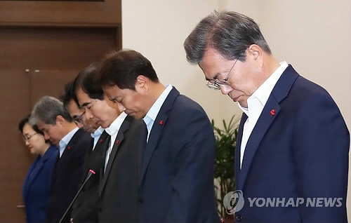 President Moon Jae-in (R) holds a moment of silence in honor of people killed in a fishing boat accident before the start of a weekly meeting with his top presidential aides at his office Cheong Wa Dae in Seoul on Dec. 4, 2017. (Yonhap)