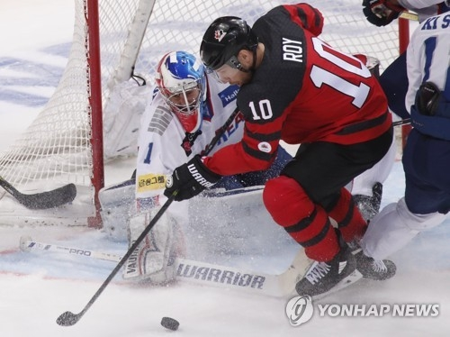 In this Reuters photo, South Korean goalie Matt Dalton (L) stops Derek Roy of Canada during the teams' Channel One Cup game at VTB Ice Palace in Moscow on Dec. 13, 2017. (Yonhap)