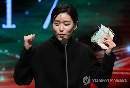 In this file photo, singer-songwriter Lee Lang celebrates on stage at the Korean Music Awards on Feb. 28, 2017, in Seoul after selling the trophy for her Best Folk Song award to an audience. (Yonhap)