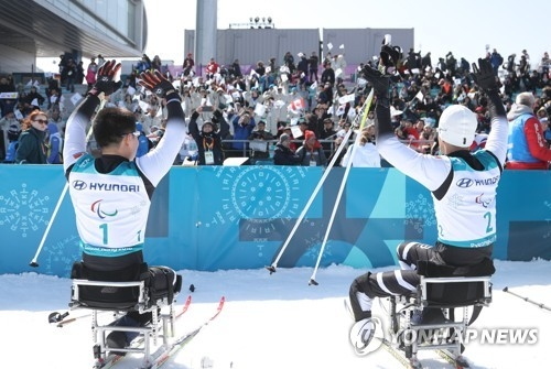 This file photo taken March 11, 2018, shows North Korean sit skiers Ma Yu-chol (R) and Kim Jong-hyon responding to fans support at Alpensia Biathlon Centre in PyeongChang, Gangwon Province, after they competed in the men's 15km sitting cross-country skiing event at the PyeongChang Paralympics. (Yonhap)