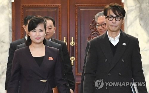 This photo, provided by South Korea's unification ministry on March 20, 2018, shows Yoon Sang (R), a South Korean composer and the chief delegate for inter-Korean talks on a South Korean art troupe's planned performance in Pyongyang, and his North Korean counterpart Hyon Song-wol (L), entering a conference room at the Tongilgak administrative building on the northern side of the truce village of Panmunjom. (Yonhap)