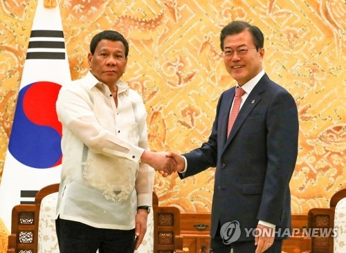 South Korean President Moon Jae-in (R) and Filipino President Rodrigo Duterte shake hands before the start of their bilateral summit at the South Korean presidential office Cheong Wa Dae in Seoul on June 4, 2018. (Yonhap)