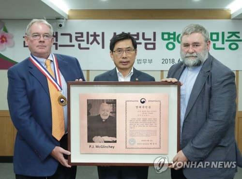 The photo shows Raymond McGlinchey (L), Justice Minister Park Sang-ki (C) and Father Michael Riordan (R), chairman of the Isidore Development Association, at the dedication ceremony for late Father Patrick McGlinchey's honorary citizenship in Seoul on June 5, 2018. (Yonhap)
