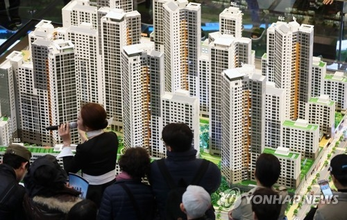 In this photo taken March 16, 2018, visitors look at a model of DH Xi Gaepo apartment buildings in southern Seoul. (Yonhap)