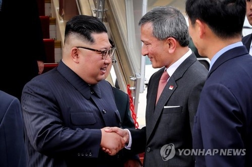 North Korean leader Kim Jong-un (L) shakes hands with Singapore's foreign minister Vivian Balakrishnan on June 10, 2018, after arriving in the city-state for a planned summit with U.S. President Donald Trump, in this photo captured from Balakrishnan's Twitter account. (Yonhap)