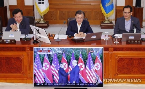 South Korean President Moon Jae-in (C) watches the historic Singapore meeting between U.S. President Donald Trump and North Korean leader Kim Jong-un on TV before the start of a weekly Cabinet meeting held at his office Cheong Wa Dae in Seoul on June 12, 2018. (Yonhap)