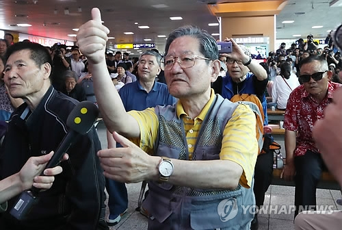 A South Korean man makes a thumbs-up gesture while watching the U.S.-North Korea summit on TV at Seoul Station on June 12, 2018. (Yonhap)