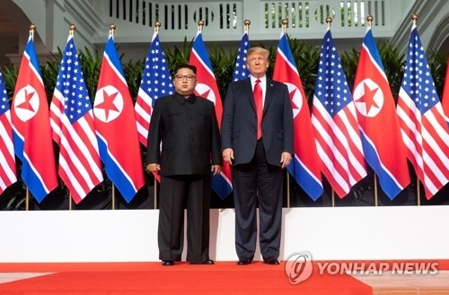 U.S. President Donald Trump (R) poses with North Korean leader Kim Jong-un at the Capella Hotel in Singapore on June 12, 2018, during their summit there, in this photo captured from the Twitter account of White House social media director Dan Scavino. (Yonhap)