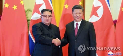 Chinese President Xi Jinping (R) shakes hands with North Korean leader Kim Jong-un during a welcoming event in Beijing on June 19, 2018, in this photo released by the North's Korean Central News Agency. (For Use Only in the Republic of Korea. No Redistribution.) (Yonhap)
