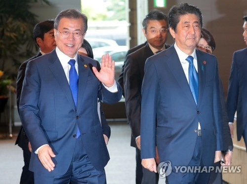 This file photo taken on May 9, 2018 shows South Korean President Moon Jae-in (L) and Japanese Prime Minister Shinzo Abe at the latter's residence in Tokyo. (Yonhap)