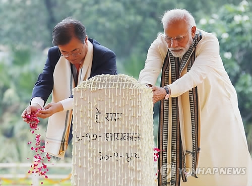 South Korean President Moon Jae-in (L) and Indian Prime Minister Narendra Modi lay flower petals in front of a monument commemorating the late Indian activist and leader Mahatma Gandhi during their joint trip to the National Gandhi Museum in New Delhi on July 9, 2018. (Yonhap)