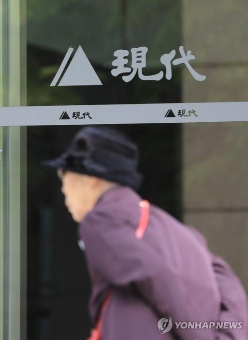 This file photo shows a woman passing the logo of Hyundai Asan at the company's headquarters in central Seoul. (Yonhap)
