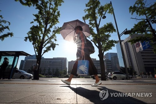 A pedestrian takes cover from the sun while walking through downtown Seoul on Aug. 1, 2018. The scorching heatwave continued on the day with no forecast of relief. (Yonhap)