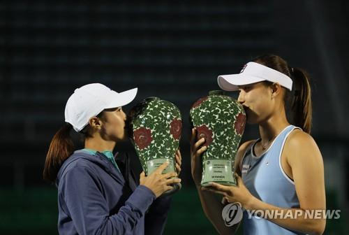 South Korean tennis players Han Na-lae (L) and Choi Ji-hee kiss their trophies after winning the women's doubles title at the Korea Open on the Women's Tennis Association Tour at Olympic Park Tennis Center in Seoul on Sept. 23, 2018. (Yonhap)