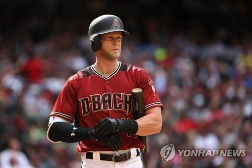 In this Getty Images file photo from April 9, 2017, Jeremy Hazelbaker, then with the Arizona Diamondbacks, adjusts his batting gloves during a Major League Baseball regular season game against the Cleveland Indians at Chase Field in Phoenix, Arizona. South Korean ball club Kia Tigers said that they've acquired Hazelbaker on a one-year, US$700,000 million deal. (Yonhap)