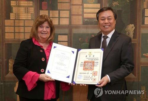 In this photo provided by the Ministry of Culture, Sports and Tourism, Gunilla Lindberg (L), head of the International Olympic Committee's Coordination Commission on the 2018 PyeongChang Winter Olympics, receives the certificate for the Maengho Medal, the second highest decoration in South Korea's Order of Sport Merit, from Sports Minister Do Jong-whan, during a ceremony at the National Museum of Korea in Seoul on Nov. 21, 2018. (Yonhap)