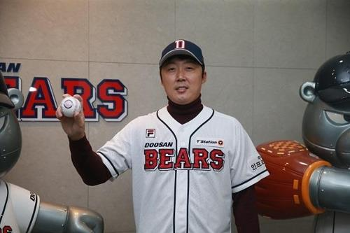 In this photo provided by the Doosan Bears baseball club on Nov. 30, 2018, Bae Young-soo, the Korea Baseball Organization team's new pitcher, poses in his new uniform next to the team's mascots at Jamsil Stadium in Seoul. (Yonhap)