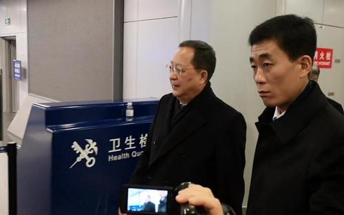 North Korean Foreign Minister Ri Yong-ho (left) heads to the departure terminal at Beijing's Capital International Airport to take a flight to Pyongyang on Dec. 11. (Yonhap)