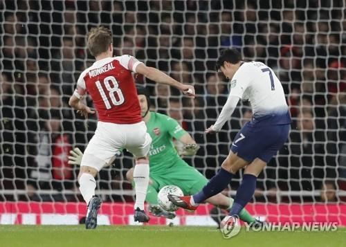 In this photo taken by the Associated Press, Tottenham's Son Heung-min (R) scores his side's first goal during the Carabao Cup quarterfinal match between Arsenal and Tottenham Hotspur at the Emirates stadium in London on Dec. 19, 2018. (Yonhap)