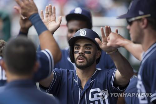 This photo taken by Getty Images shows Carlos Asuaje of the San Diego Padres celebrating with his teammates in the dugout after scoring a run in the top of the first inning against the Philadelphia Phillies at Citizens Bank Park on July 22, 2018, in Philadelphia, Pennsylvania. (Yonhap)