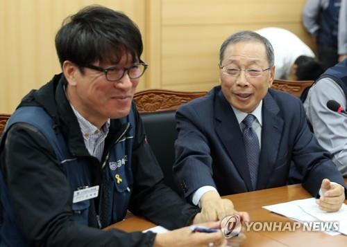 In this file photo, taken Sept. 14, 2018, SsangYong Motor CEO Choi Jong-sik (R) holds the hand of Kim Deuk-joong, chief of the SsangYong Motor branch of the Korean Metal Workers' Union, after signing an agreement to rehire 119 fired workers by 2019. (Yonhap)