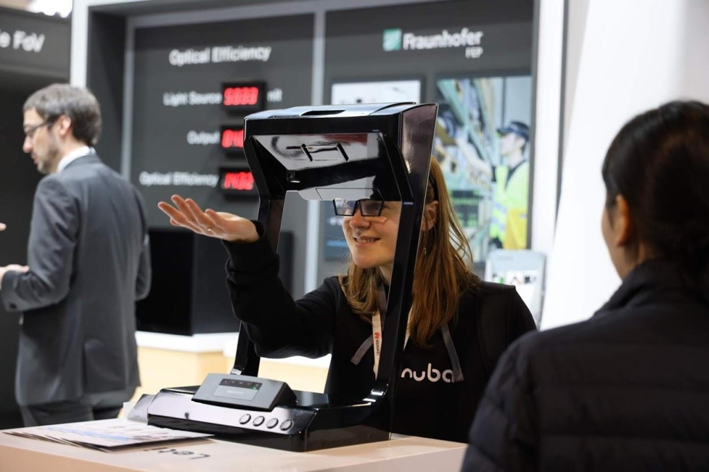 A visitor to LetinAR's exhibition booth at MWC Barcelona experiences its AR display, in this photo provided by the company on March 13, 2019. (Yonhap)