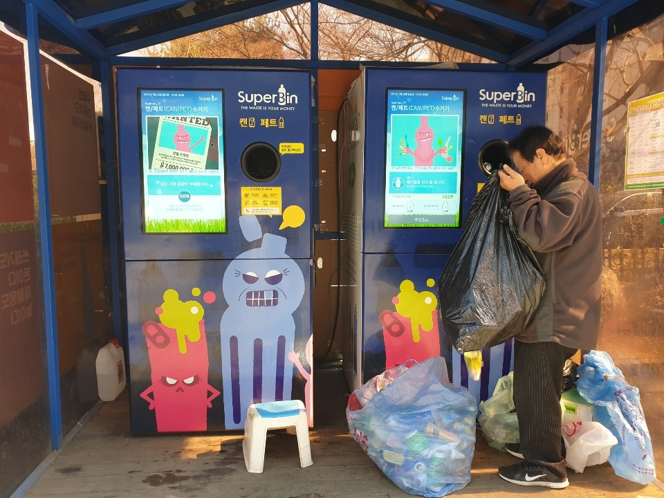 A local resident puts plastic bottles in Superbin's reverse vending machine, Nephron, in a park in Gwacheon, south of Seoul, on March 24, 2019. (Yonhap)