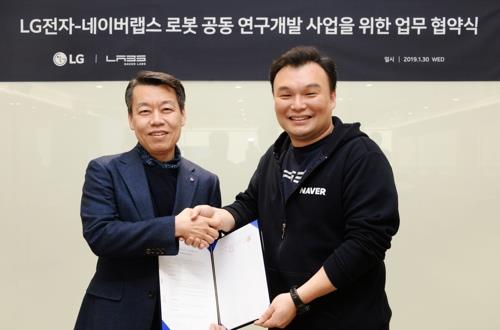 Seok Sang-ok (R), CEO of Naver LABS, shakes hands with Roh Jin-seo, head of robotics business at LG Electronics Inc., after signing a memorandum of understanding on cooperation in robotics technology, in Seoul, on Jan. 30, 2019. (Yonhap)