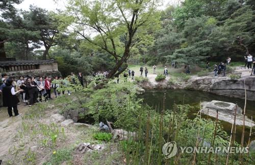 This photo shows visitors on a guided tour next to a rocky pond in the center of Seongnagwon, a typical traditional Korean garden in Seoul, on April 23, 2019. (Yonhap)