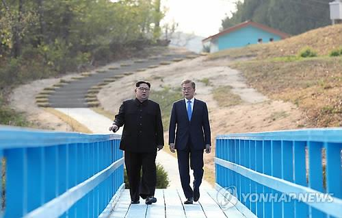 This file photo shows South Korean President Moon Jae-in (R) and North Korean leader Kim Jong-un taking a walk together at Panmunjom on April 27, 2018. (Yonhap)