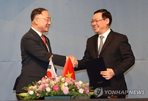 Hong Nam-ki (L), the minister of economy and finance, shakes hands with Vietnam's Deputy Prime Minister Vuong Dinh Hue after their talks at a Seoul hotel on June 21, 2019, in this photo provided by the ministry. (PHOTO NOT FOR SALE) (Yonhap)