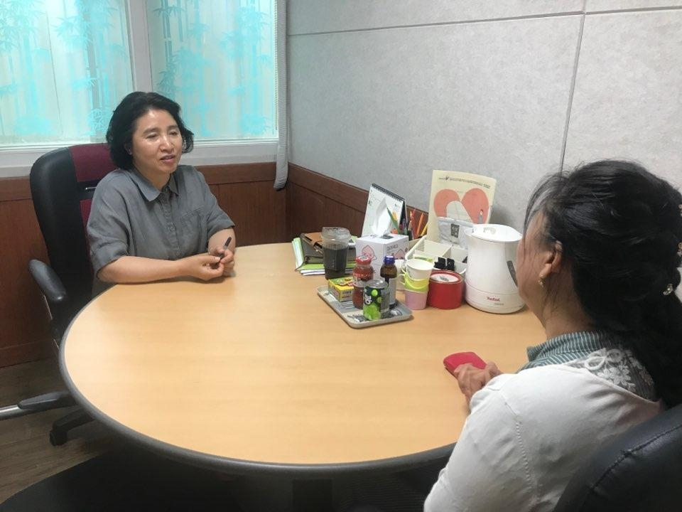 Park Kyung-hui (L), a counselor of the Korea Hana Foundation, talks with a North Korean defector, during a psychological therapy session. (Yonhap)