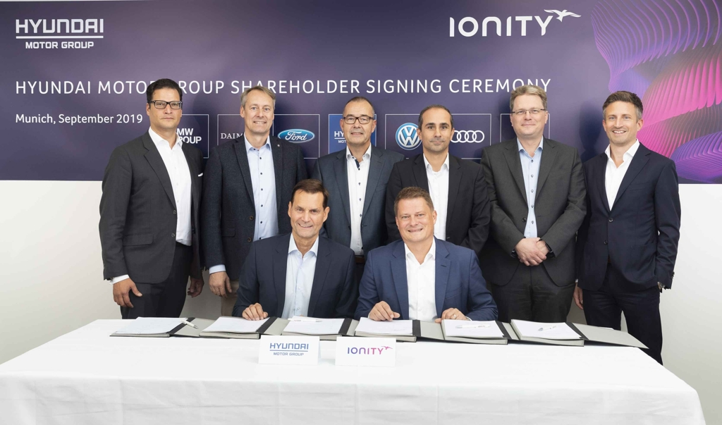 In this photo provided by Hyundai Motor Group, Thomas Schemera (front row, L), Executive Vice President at Hyundai Motor Group, and IONITY CEO Michael Hajesch (front row, R) pose for a photo with officials from BMW, Ford, Mercedes-Benz and Porsche after signing a strategic partnership agreement at IONITY's headquarters in Munich, Germany, on Sept. 6, 2019. (PHOTO NOT FOR SALE) (Yonhap)