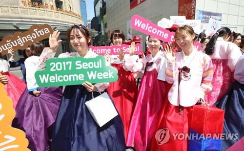 This file photo shows tourist officials dressed in traditional Korean costume promoting the 2017 Seoul Welcome Week in Myeongdong in Seoul. (Yonhap)