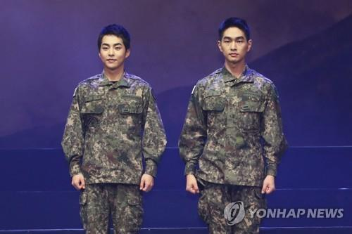 "EXO's Xiumin (L) and SHINee's Onew pose for photos during a press showcase of a military musical, ""Return: The Promise of the Day,"" on Sept. 24, 2019. (Yonhap)"