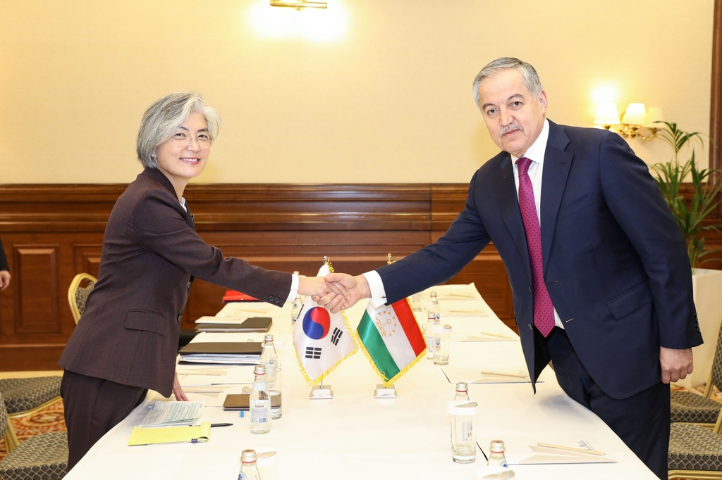 Foreign Minister Kang Kyung-wha (L) shakes hands with her Tajikistani counterpart, Sirodjiddin Muhriddin, before their talks in Nur-Sultan on Oct. 16, 2019 in this photo provided by her ministry. (PHOTO NOT FOR SALE) (Yonhap)