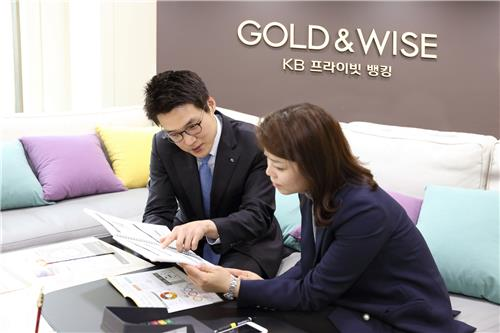 This undated photo provided by KB Kookmin Bank shows a private banker (L) explaining a financial product to a customer in a meeting room of the bank's private banking center in Myeongdong, central Seoul. (PHOTO NOT FOR SALE) (Yonhap)