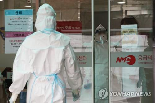 Medical staff at the National Medical Center wear protective masks and suits as they prepare to check people for the novel coronavirus in this photo taken on Jan. 29, 2020. (Yonhap)