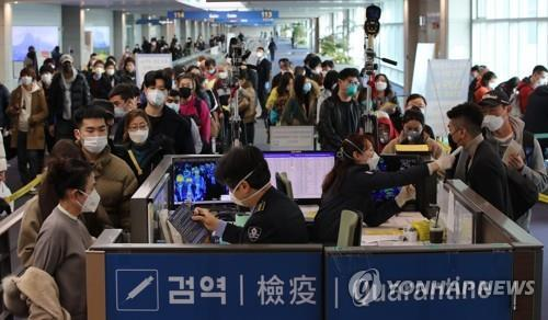 People wearing masks wait in line to pass the quarantine checkpoint at Incheon International Airport, west of Seoul, on Jan. 29, 2020. (Yonhap)