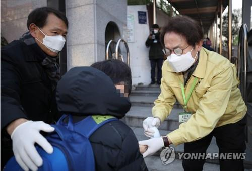 Cho Hee-yeon (R), the superintendent of the Seoul Metropolitan Office of Education, sprays sanitizer on a student's hands at Bongeun Elementary School in southern Seoul on Feb. 3, 2020. (Yonhap)